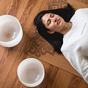 Meditating woman on a natural cork mat with sound bowl really showing self love