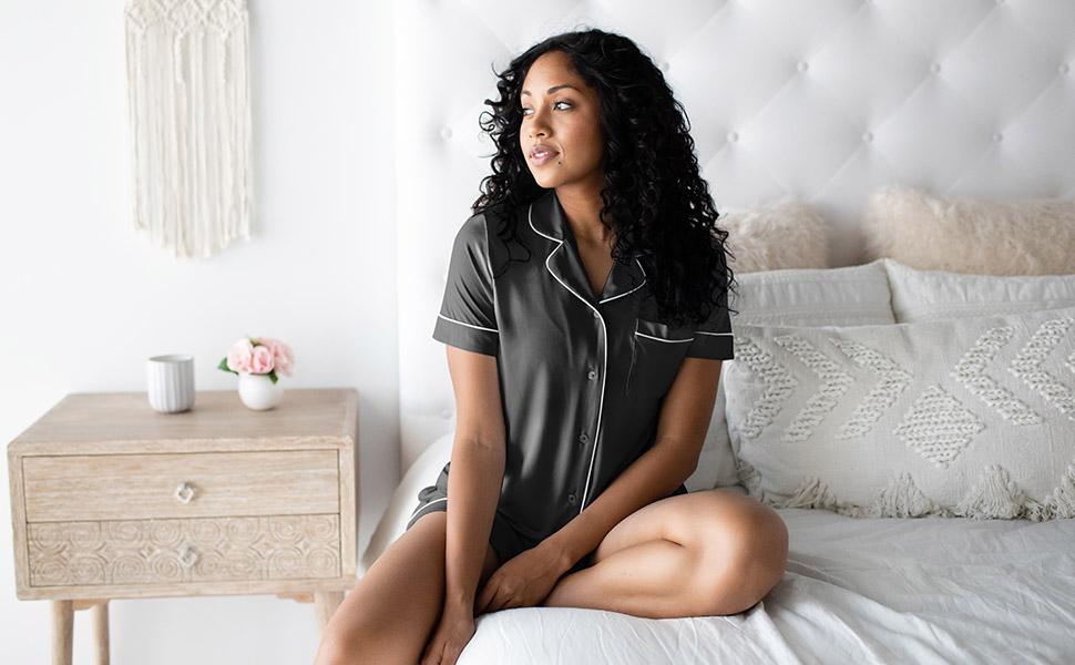 Woman wearing black short sleeve pajama set sitting on bed