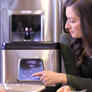 woman setting time and temperature on Perfecta sous vide machine using touch controls