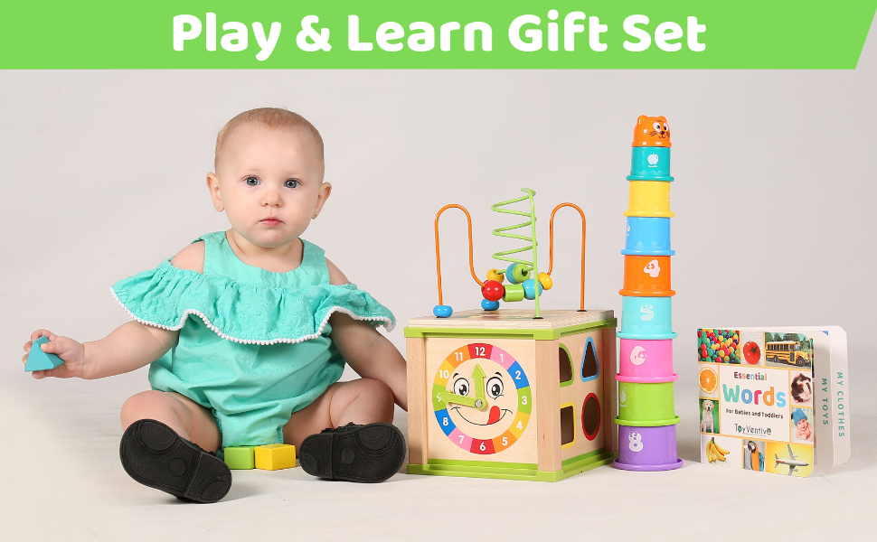 Baby girl holding shapes and sitting next to activity cube tower of stacking cups and board board