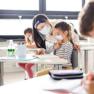 teacher and student working in a classroom with face shield mask hand sanitizer