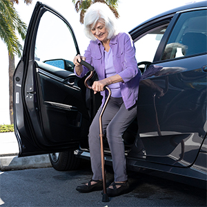 Standing up out of a car with walking cane
