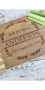 custom engraved bamboo cutting board for wedding shown in kitchen with first & last names + date