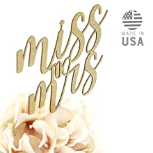 gold miss to mrs cake topper shown in floral centerpiece arrangement