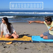 Girl and Boy on beach, each of them sitting on an ECCOSOPHY pocket blanket