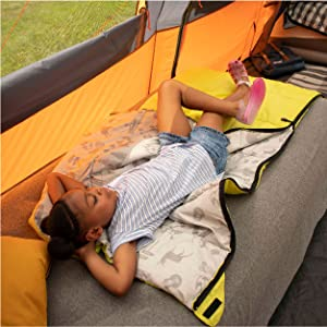 Young girl laying on green youth camp bag