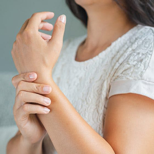 Young woman holding her wrist in pain