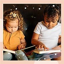 toddler girl reading a sound book