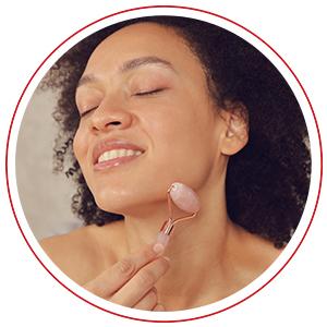 Ethnic woman using quartz roller on her cheeks