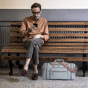 Man sitting on a bench with his nicely packed duffel storage for the overnight weekend stay