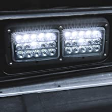 """4pc 45W 6""""x4"""" LED Headlight with Black Housing on Black Bus with close up of Low Beam."""