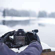 Gloves with camera near snowy lake