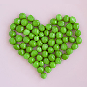 Green peas image in heart shape on pink background