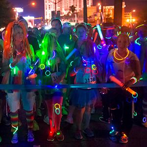 Un gruppo di persone si diverte a indossare accessori luminosi dalla testa ai piedi.