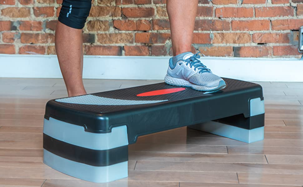 Large stepper at an angle, on wood floor, an athlete has 1 foot on the stepper and 1 on the ground
