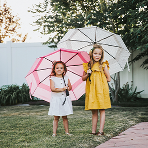 Two girls holding EEZY umbrellas smiling in the backyard