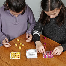 Two girls playing TENZI dice game in class learning number recognition