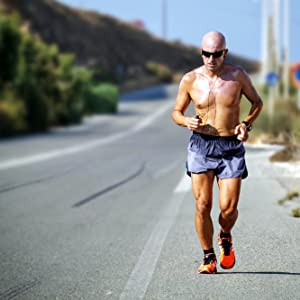 Older male running along the side of a road
