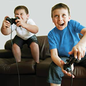 Two boys playing games by themselves on the couch
