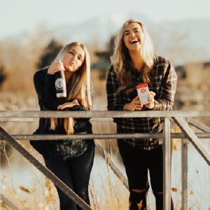Two women laughing and leaning on a fence outside.