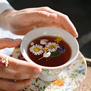 Woman holding cup of chamomile tea