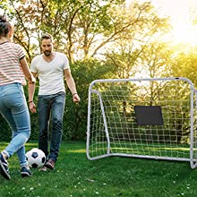 a couple playing soccer ball in front of the soccer goal