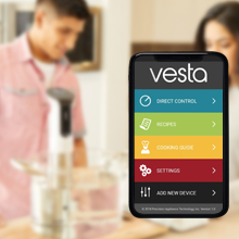 smartphone showing the Vesta app with people in the kitchen in background