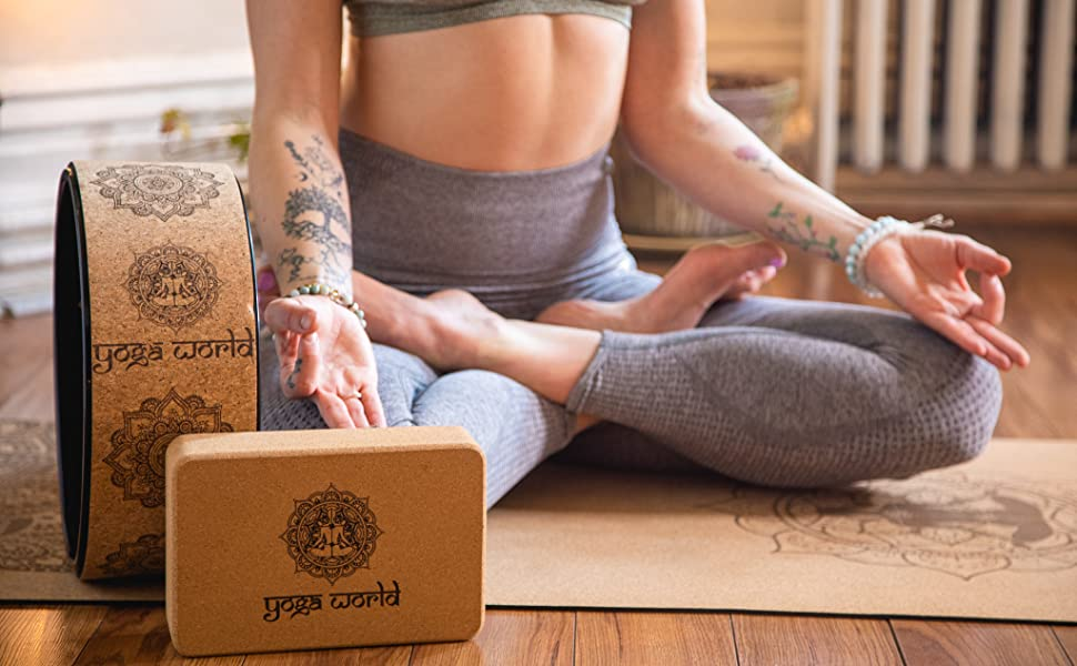Lotus position on cork yoga mat with wheel and block set