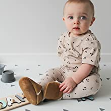 Dotty Fish Fleece Lined Suede Slippers for babies and infants, baby wearing tan suede slippers