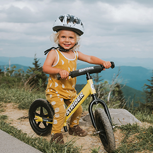 Young girl in yellow, riding the Sport 12 bike in the outdoors
