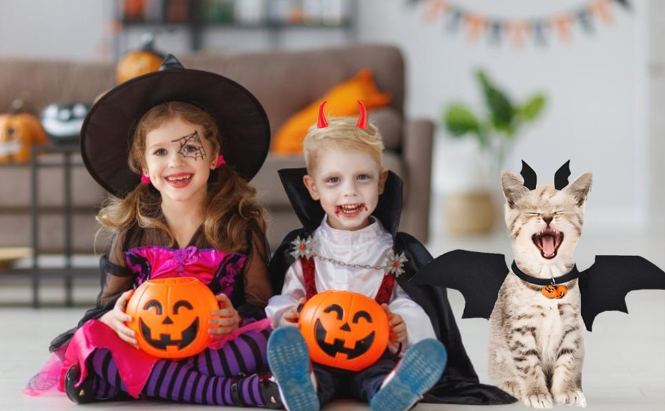 There is a cat wearing a halloween bat wings with two kids.