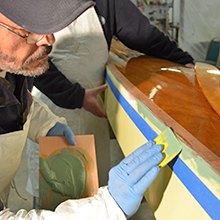 Applying TotalBoat TotalFair Epoxy Fairing Compound to even out the surface on a wooden kayak.