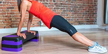 Athlete performing reverse pushups on a purple step. On wooden floor, brick wall background
