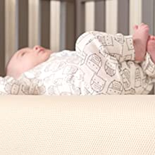 Baby on crib mattress in crib
