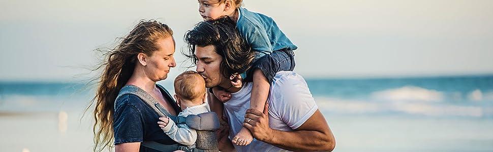Moeder houdt baby in je plus me draagzak met papa kussen zijn hoofd