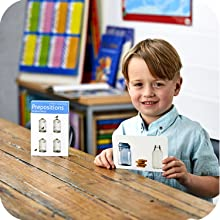 Image of boy holding a flashcard with the box just behind him.