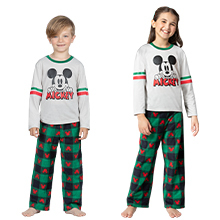 Boy and girl in matching green and red mickey pajamas on white background