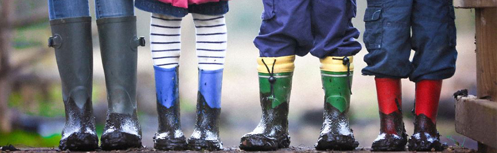 Young children standing in mud wearing rubber rain boots