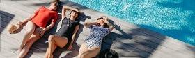 Three women in bikinis are sunbathing by the pool