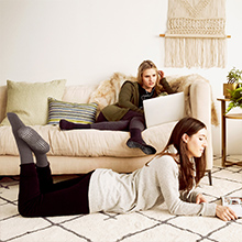 Two women wearing comfy slipper socks at home