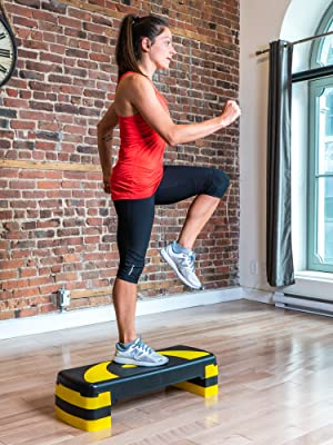 Stepper, at an angle, on wooden floor, brick wall behind, athlete with 1 foot on, 1 foot in the air