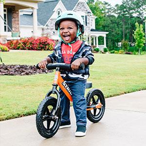 Young boy riding orange sport 12 bike