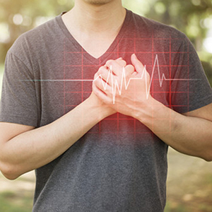 Man in T-shirt covering his heart with his hands