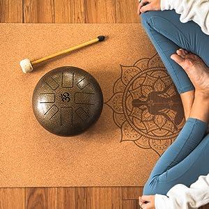 Beautiful yoga mandala prints on cork high density yoga mat being used to meditate with Tibetan drum