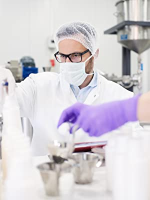 man in lab wearing face mask, hoding test tube