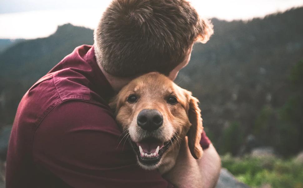 man hugging his dog
