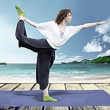 Woman doing yoga pose in green Pakari socks on boardwalk in front of sea.