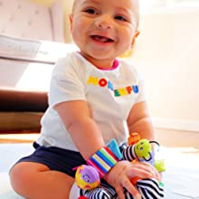 Baby wearing baby cheeks rattle set, smiling happily at camera