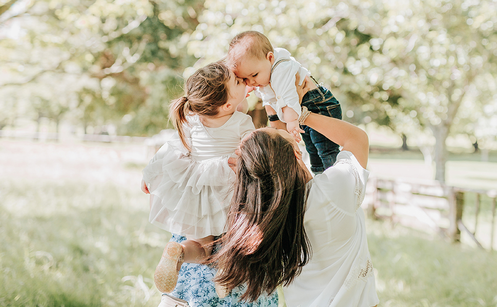 Main photo capturing a beautiful family moment of young daughter kissing her baby brother.