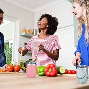 Three women cutting vegetables at kitchen table. Pink and marble wine tumbler on table.